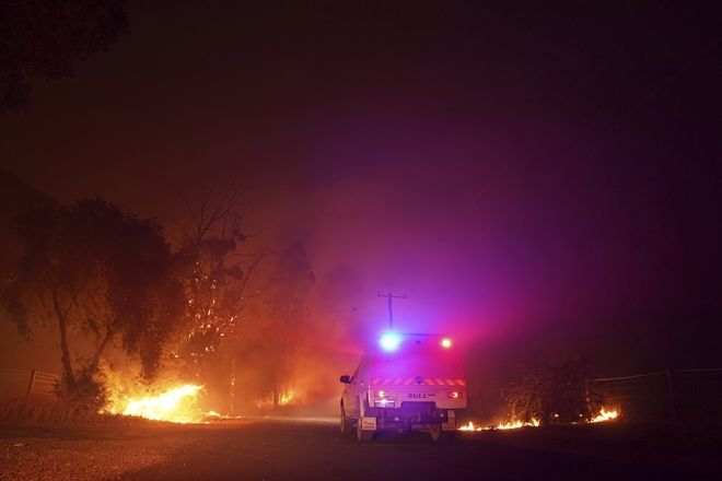 In this photo provided by Department of Fire and Emergency Services, an emergency vehicle attends a fire at Wooroloo, near Perth, Australia, Monday, Feb. 1, 2021. An out-of-control wildfire burning northeast of the Australian west coast city of Perth has destroyed an estimated 30 homes and was threatening more Tuesday, with many locals across the region told it is too late to leave. (Evan Collis/DFES via AP)