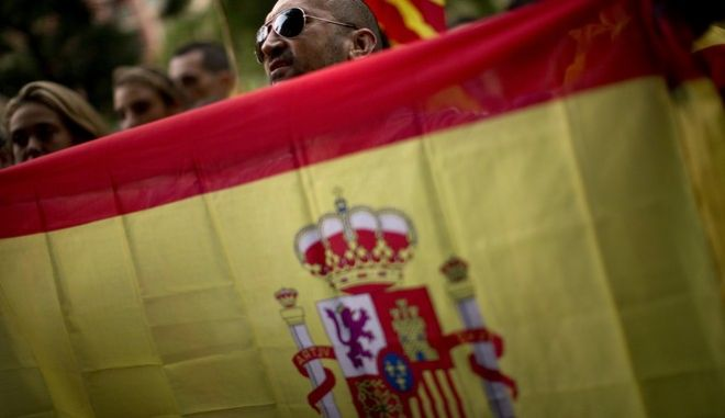 Right wing demonstrators hold Spanish flags during a protest against the Oct. 1 vote, in Barcelona, Spain Friday, Sept. 22, 2017. Dozens of anti independence people demonstrate waving Spanish flags and shouting slogans against the Oct.1 vote in front of Catalan National Assembly ANC, an organization that seeks the political independence of Catalonia from Spain. (AP Photo/Emilio Morenatti)