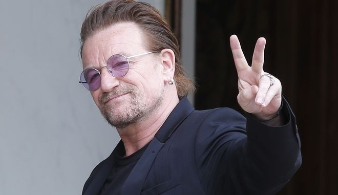 FILE - In this Monday, July 24, 2017 file photo, U2 singer Bono makes a peace sign as he arrives for a meeting at the Elysee Palace, in Paris, France. Leaked papers revealing investments in tax havens by the world's wealthy suggest U2 frontman Bono used a company based in low-tax Malta to buy part of a shopping mall in Lithuania, it was announced on Monday Nov. 6. (AP Photo/Michel Euler, file)