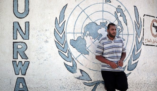 """A Palestinian Hamas supporter stands next to a wall graffiti as he attends a demonstration against the U.N. Relief and Works Agency (UNRWA) lack of funding, outside their Gaza Headquarters in Gaza City, Friday, Aug. 14, 2015. The UN agency helping Palestinian refugees says a $101 million funding gap could keep 500,000 Palestinian students out of school this fall. The deputy chief of the U.N. Relief and Works Agency, Sandra Mitchell, said Monday that """"if funding does not arrive"""" this month, the agency could delay the start of the school year. (AP Photo/ Khalil Hamra)"""