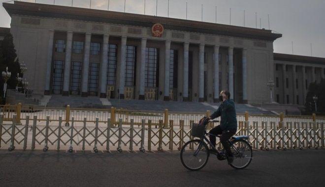 Άνδρας με μάσκα κάνει ποδήλατο στο Πεκίνο (AP Photo/Mark Schiefelbein)