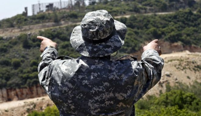 A Hezbollah officer, who identified himself as Ehab, explains to journalists about the defensive measures established by the Israeli forces to prevent against any Hezbollah infiltration into Israel, at the Lebanese-Israeli border near the village of Labbouneh, south Lebanon, Thursday, April 20, 2017. Hezbollah organized a media tour along the border with Israel meant to provide an insight into defensive measures established by the Israeli forces along the southern frontier in the past year in preparation for any future conflict. The border tour is the first since an inconclusive month long war between Israel and Hezbollah in 2006, and comes amid heightened tensions along the border between the old adversaries, with each side promising to inflict massive casualties on the other in any upcoming war. (AP Photo/Hussein Malla)