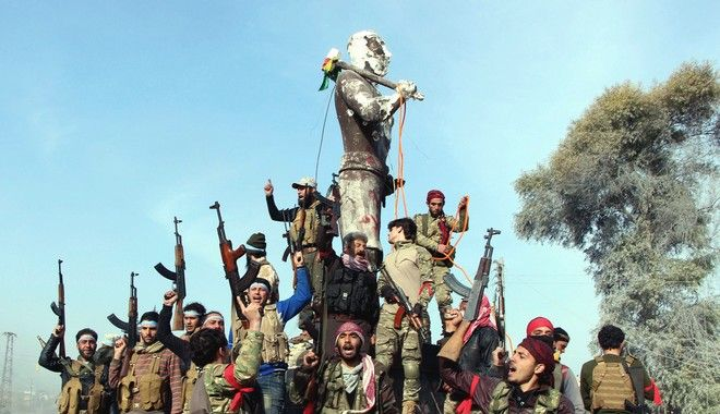 Turkey-backed Free Syrian Army soldiers celebrate around a statue of Kawa, a mythology figure in Kurdish culture as they prepare to destroy it in city center of Afrin, northwestern Syria, early Sunday, March 18, 2018. Turkey's President Recep Tayyip Erdogan said Sunday that allied Syrian forces have taken