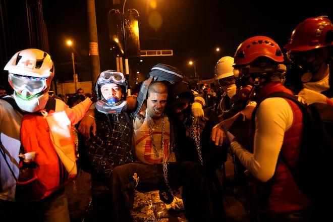 Οι εργαζόμενοι του Ερυθρού Σταυρού βοηθούν έναν διαδηλωτή που τραυματίστηκε κατά τη διάρκεια συγκρούσεων με την αστυνομία στην Plaza San Martin