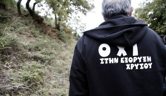 "A man wearing a hoody that reads ""Not in gold mining"". Peaceful protest against the construction of the gold mines in northern Greece's Halkidiki peninsula in position Skouries. Dozens of residents of the nearby villages of Ierissos and Ouranoupoli, as well as protesters who arrived by coaches and cars from Thessaloniki, approached the forest in Skouries, where Hellenic Gold, a subsidiary of Canadian firm Eldorado Gold, has begun mining activity that locals are appealing against. The residents of the village Megali Panagia have been divided into two sides, those who react to the operation of gold mines because of the enormous ecological disaster and those who are in favor because in the future will work in the mines. Hellenic Gold has been awarded an area of 26,400 hectares, of which 410 is forest land. Almost all the trees in the forest will be cut down as part of the mining firms plan to extract gold. The company says it will replant trees when it finishes its work./       ""   "".              .           ,            ,     ,   Hellenic Gold,     Eldorado Gold,            .           ,                         ."