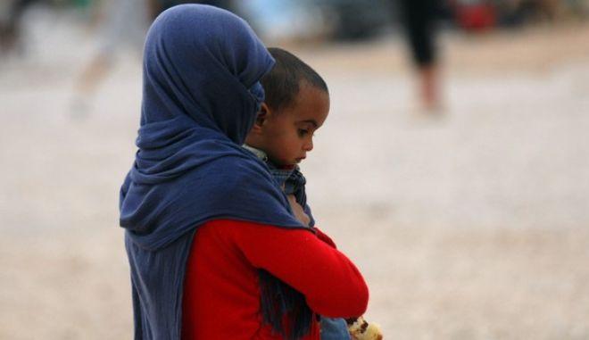 Γυναίκα πρόσφυγας περπατά έχοντας στην αγκαλιά της το μωρό παιδί της