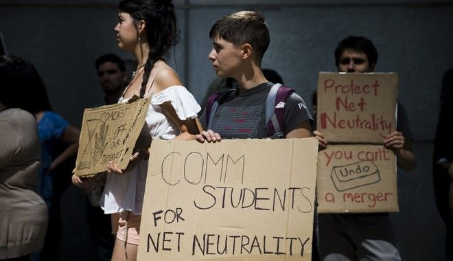 """Protesters demonstrate across the street from the Comcast Center Monday, Sept. 15, 2014, in Philadelphia. Demonstrators expressed opposition to the proposed merger of communications companies Comcast Corp. and Time Warner Cable Inc., and called for further Federal Communications Commission regulation of Internet traffic to support """"net neutrality,"""" advocates who want strong government protections for the open Internet. (AP Photo/Matt Rourke)"""