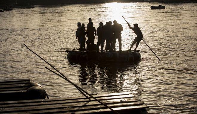 Σε αυτοσχέδια σχεδία μετανάστες προσπαθούν να διασχίσουν τον ποταμό Suchaitei στο Μεξικό.