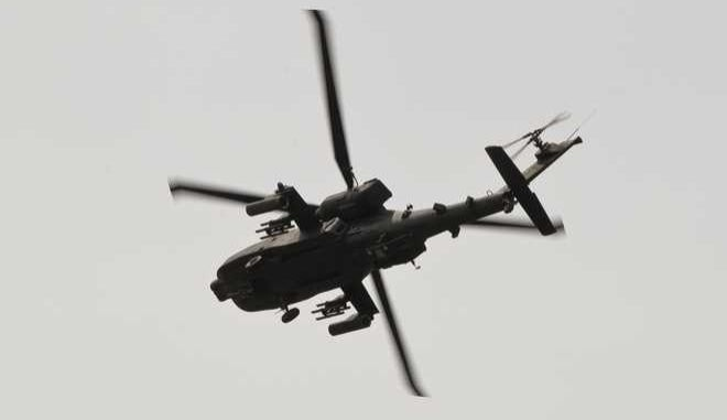 An US military Apache attack helicopter flies above a road outside Ploiesti, Romania, Wednesday, May 13, 2015. Members of the US military took part in an exercise dubbed the Cavalry March, a drive from southern Romania to a training range in the central region of Transylvania, involving 400 servicemen and 80 armored combat vehicles.(AP Photo/Vadim Ghirda)