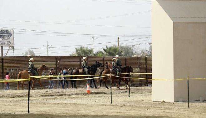 A group of people are detained by Border Patrol agents on horseback after crossing the border illegally from Tijuana, Mexico, near prototypes for a border wall, right, are being constructed Thursday, Oct. 19, 2017, in San Diego. Companies are nearing an Oct. 26 deadline to finish building eight prototypes of President Donald Trump's proposed border wall with Mexico. (AP Photo/Gregory Bull)