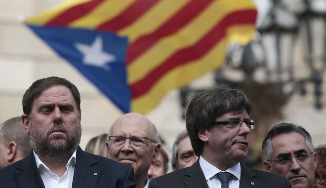 Catalan regional Vice-President, Oriol Junqueras, left, and Catalan President, Carles Puigdemont, attend during a protest called by pro-independence outside of the Palau Generalitat in Barcelona, Spain, Monday, Oct. 2, 2017. Catalonia's government will hold a closed-door Cabinet meeting Monday to discuss the next steps in its plan to declare independence from Spain following a disputed referendum marred by violence. (AP Photo/Manu Fernandez)