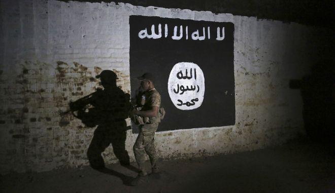 Ιρακινός στρατιώτης με φόντο σημεία του Ισλαμικού Κράτους στη Μοσούλη