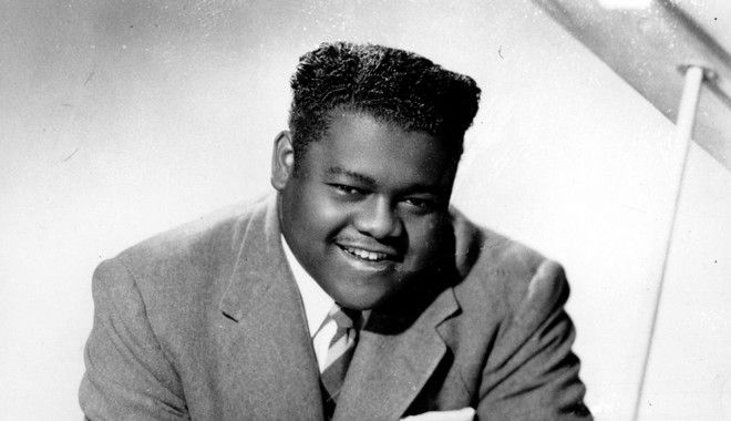 This is a 1956 photograph of singer, composer and pianist Fats Domino. He popularized rock and roll in the 1950s and early 1960s with his songs that include