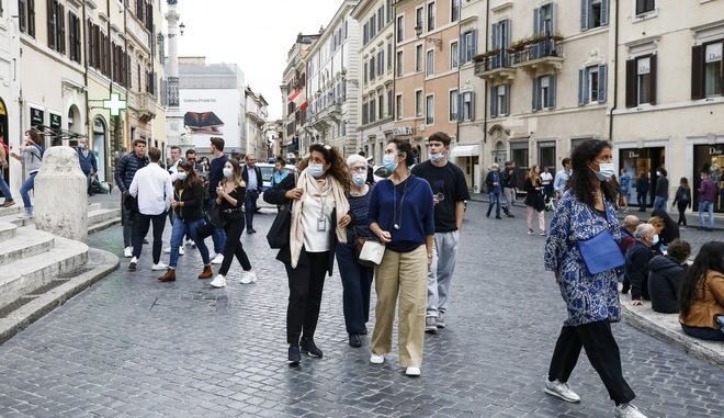 People wearing masks for protection against COVID-19 walk in Rome, Friday, Oct. 2, 2020. Italian Premier Giuseppe Conte said Friday that he would consider making it mandatory to wear masks outdoors after Lazio, the region that includes Rome, put such an order into effect starting Saturday. (Cecilia Fabiano/LaPresse via AP)