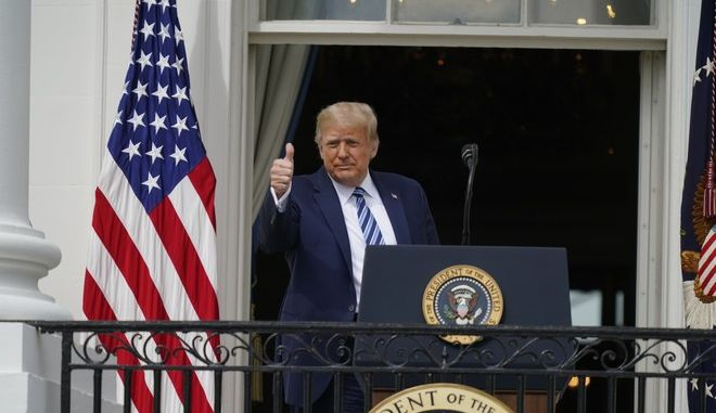 President Donald Trump gives a thumbs up from the Blue Room Balcony of the White House to a crowd of supporters, Saturday, Oct. 10, 2020, in Washington. (AP Photo/Alex Brandon)