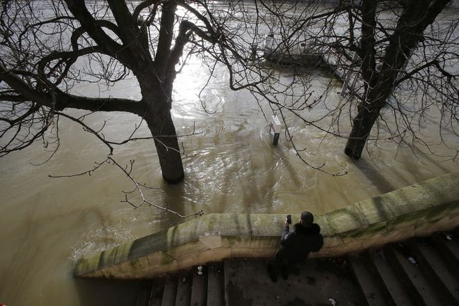 A man take a photo of the Seiner river with his mobile phone in Paris, France, Friday, Jan. 26, 2018. The Paris region has been deeply affected by the floods that hit the country over the past week, but in Paris, it was business as usual. (AP Photo/Michel Euler)