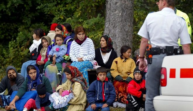 Romanian illegal immigrants wait alongside a road in Thierrens, Vaud, Switzerland, Sunday, Sept. 22, 2002, watched by police officers. The police of the canton Vaud has picked up 89 Romanian illegal immigrants, among them 43 children, Saturday night and Sunday morning. They had been dropped off by a fugitive driver of a truck on the road between Thierrens and Neyruz in the canton Vaud. The Romanians are seeking political asylum in Switzerland.  (AP Photo/Keystone/Fabrice Coffrini)