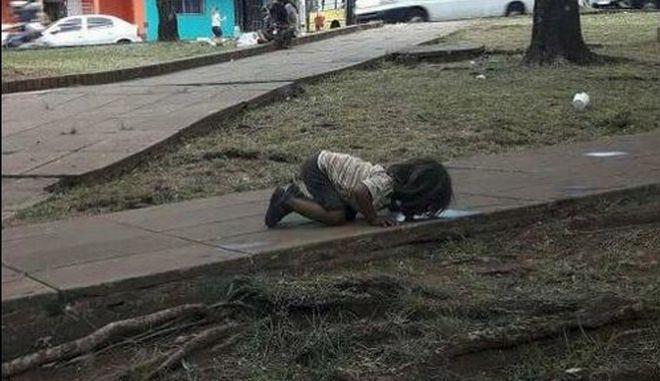 Φωτογραφία σοκ: Κοριτσάκι πίνει νερό από λακκούβα σε πεζοδρόμιο