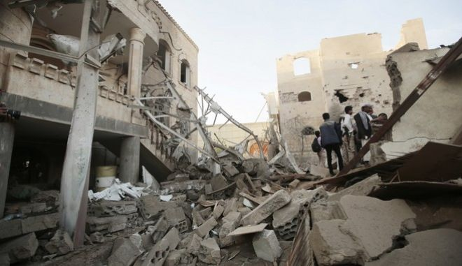 FILE -- In this Jun. 9, 2017 file photo, people stand on the rubble of houses destroyed by Saudi-led airstrikes in Sanaa, Yemen. More than two years of civil war have led to continually compounding disasters in Yemen. Fighting rages on in a deadly stalemate, the economy has been bombed into ruins, hunger is widespread, and a new misery has been added: Cholera, the worlds biggest current outbreak with more than 200,000 cases. (AP Photo/Hani Mohammed, File)
