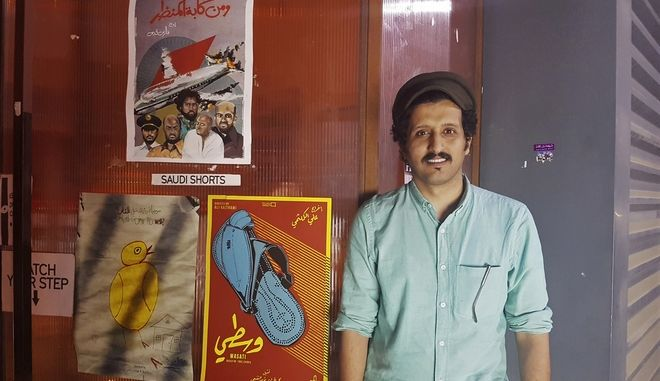 "In this Friday, Aug. 25, 2017 photo, Saudi filmmaker Ali Kalthami stands next to the poster for his film ""Wasati"" or ""Moderate"" and two other Saudi short films recently shown at Cinema Akil in Dubai, United Arab Emirates. Saudi Arabia has no movie theaters, but young Saudi filmmakers are on course to change that. As the kingdom cautiously embraces greater forms of entertainment, local filmmakers are creating a new frontier in Saudi art, using the internet to screen films and pushing boundaries of expression -- often with surprise backing from top royals. (AP Photo/Aya Batrawy)"