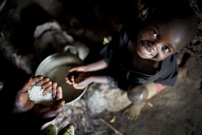 Elisa, 6 years old, who has ten brothers and sisters and whose father is dead, poses for a photograph while helping her mother preparing their daily meal of rice at their home in Buhoro in  Idjwi Sud, DR Congo Thursday, Sept. 25, 2014