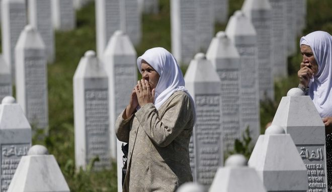 Bosnian Muslim women pray as they walking among gravestones during a funeral ceremony for dozens of newly identified victims of the 1995 massacre, at the memorial centre of Potocari near Srebrenica, 150 kms north east of Sarajevo, Bosnia, Tuesday, July 11, 2017. Twenty two years ago, on July 11, 1995, Serb troops overran the eastern Bosnian Muslim enclave of Srebrenica and executed some 8,000 Muslim men and boys, which international courts have labeled as an act of genocide. (AP Photo/Amel Emric)
