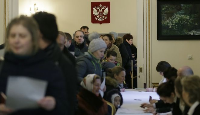 People queue to cast their votes in the Russian presidential election at the Russian Embassy in London, Sunday, March 18, 2018. Russians are voting in a presidential election in which Vladimir Putin is seeking a fourth term in the Kremlin. (AP Photo/Tim Ireland)