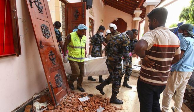 Διασώστες μεταφέρουν πτώματα μεσα από εκκλησία στη Σρι Λάνκα