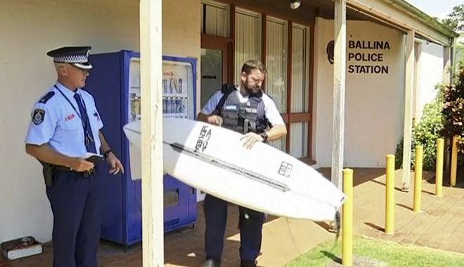 Αστυνομικοί κρατούν τη σανίδα ενός σέρφερ που δέχθηκε επίθεση από καρχαρία