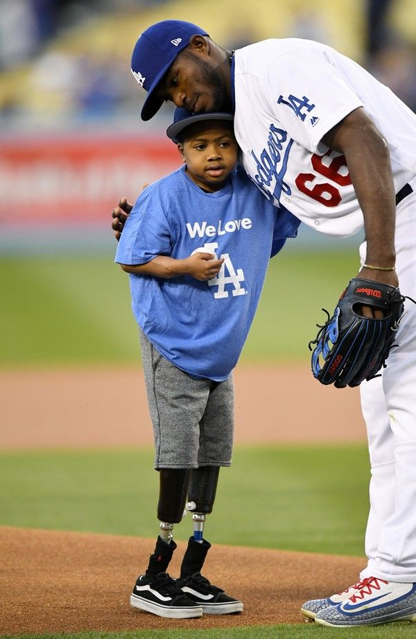 Zion Harvey, 10, gets a hug from Los Angeles Dodgers' Yasiel Puig after throwing out the ceremonial first pitch at a game between the Dodgers and the Arizona Diamondbacks, Friday, April 14, 2017, in Los Angeles. Harvey lost parts of his legs to a sepsis infection. (AP Photo/Mark J. Terrill)