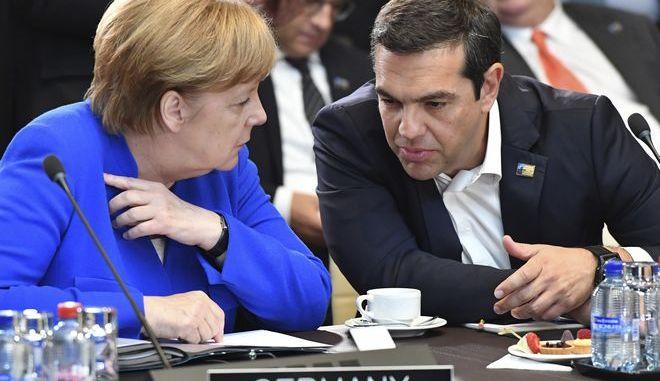 O Αλέξης Τσίπρας και η Άγκελα Μέρκελ συνομιλούν κατά τη διάρκεια της Συνόδου Κορυφής του ΝΑΤΟ, τον περασμένο Ιούλιο