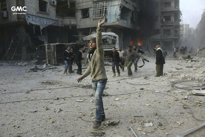 In this photo released on Wednesday Feb. 21, 2018, provided by the Syrian anti-government activist group Ghouta Media Center, which has been authenticated based on its contents and other AP reporting, shows Syrian citizens carry a victim during airstrikes and shelling by Syrian government forces, in Ghouta, suburb of Damascus, Syria. New airstrikes and shelling on the besieged, rebel-held suburbs of the Syrian capital killed at least 10 people on Wednesday, a rescue organization and a monitoring group said. (Ghouta Media Center via AP)