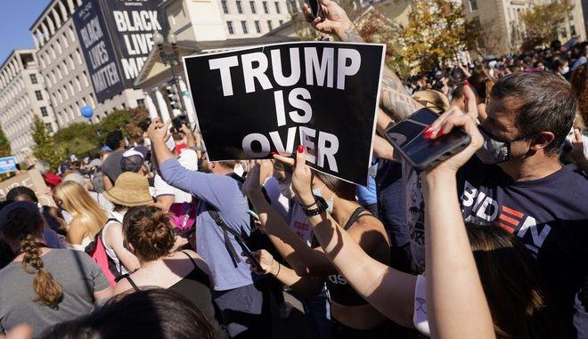 """Κόσμος πανηγυρίζει γα τη νίκη του Τζο Μπάιντεν. Πλακάτ γράφει """"Ο Τραμπ τελείωσε"""""""