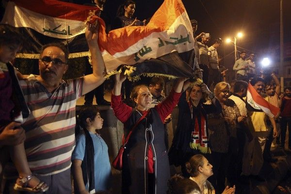 Iraqis celebrate in Tahrir square while holding national flags as they wait for the final announcement of the defeat of the Islamic state militants, in Baghdad, Iraq, Sunday, July 9, 2017. Backed by the U.S.-led coalition, Iraq launched the operation to retake Mosul from Islamic State militants in October. (AP Photo/Karim Kadim)