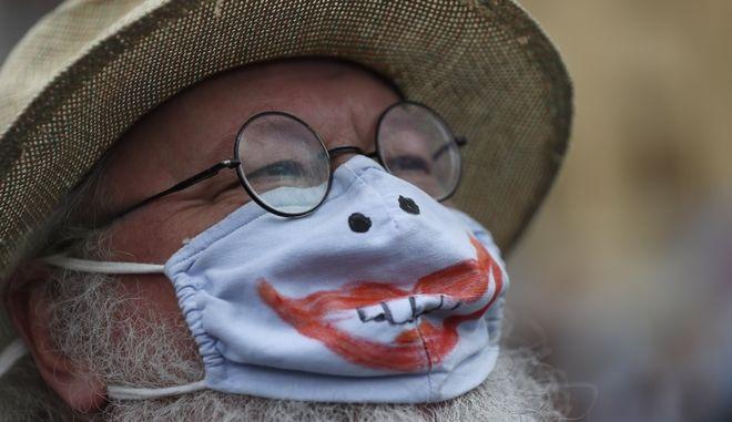 Άνδρας με μάσκα σε διαδήλωση