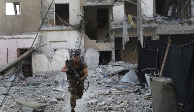 A U.S.-backed Syrian Democratic Forces fighter runs in front of a damaged building as he crosses a street on the front line, in Raqqa city, Syria, Thursday, July 27, 2017. U.S.-backed Syrian fighters have captured almost half of the Islamic State group's de facto capital of Raqqa, but the push into the northern city has slowed due to stiff resistance and large amounts of explosives planted by extremists, a spokeswoman for the fighters and monitors said Thursday. (AP Photo/Hussein Malla)