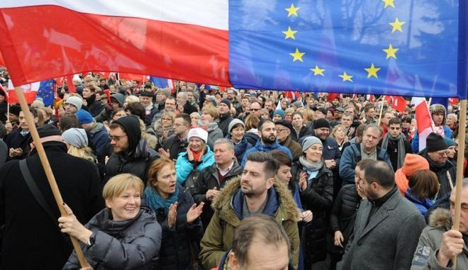 Protesters wave Polish and European Union flags during an anti government demonstration in Warsaw, Poland, Saturday, Dec. 19, 2015. Thousands of Poles participated in demonstrations across Poland to protest moves by the new right-wing government to neutralize the Constitutional Tribunal as a check on its power. (AP Photo/Alik Keplicz)