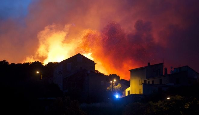 In this image dated Monday, July 24, 2017, a forest fire rages on a hillside above the village of Ortale in Corsica, France. Hundreds of firefighters are battling blazes fanned by high winds in more than a dozen zones in the Riviera region of southern France. (AP Photo/Raphael Poletti)