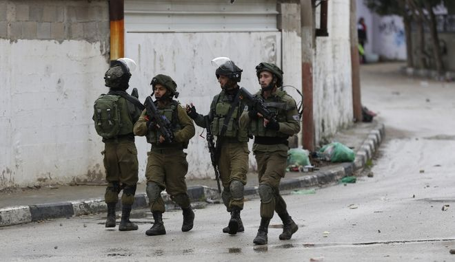 Members of Israeli armed forces patrol through the streets of the West Bank city of Jenin, Thursday, Jan. 18, 2018. Israeli police say special forces killed a Palestinian gunman in the West Bank who allegedly killed an Israeli in a drive-by shooting earlier this month. (AP Photo/Majdi Mohammed)