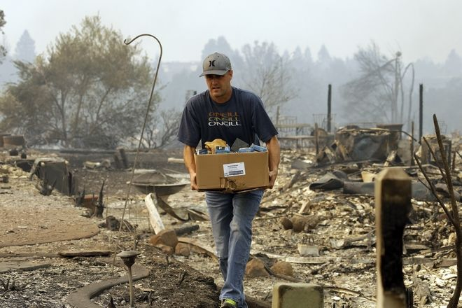 A man retrieves belongings from a safe where his house once stood in the Fountaingrove area of Santa Rosa, Calif., on Monday, Oct. 9, 2017. Wildfires whipped by powerful winds swept through Northern California early Monday, sending residents on a headlong flight to safety through smoke and flames as homes burned. (AP Photo/Ben Margot)