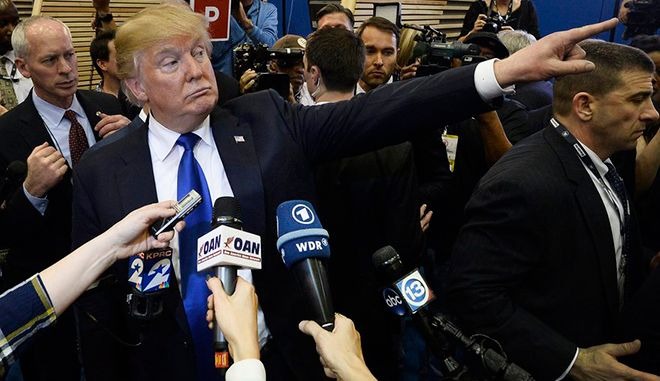 epaselect epa05181226 US Republican presidential candidate Donald Trump gestures as he talks to members of the media in the spin room after the CNN Republican Presidential Primary Debate at the University of Houston's Moores School of Music Opera House in Houston, Texas, USA, 25 February 2016. This is the final debate before the Super Tuesday elections across the country.  EPA/LARRY W. SMITH