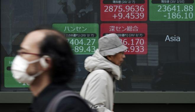 Άνθρωποι έξω από πίνακα χρηματιστηριακών συναλλαγών στο Τόκιο