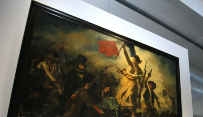 """FILE - This Tuesday, Dec. 4, 2012, file photo shows France's President Francois Hollande in front of """"Liberty Leading the People"""", a painting by Eugene Delacroix during the inauguration of the Louvre Museum in Lens, northern France. A visitor to the Louvre's newest extension, in northern France, has been detained after scrawling an inscription in marker on the famed canvas of Eugene Delacroix """"Liberty Leading the People"""". The 28-year-old woman was immediately seized by a guard and another visitor, then handed over to police, according to a statement from the Louvre-Lens on Friday Feb 8 2013. It said the painting should be easily cleaned. (AP Photo/Michel Spingler, File)"""