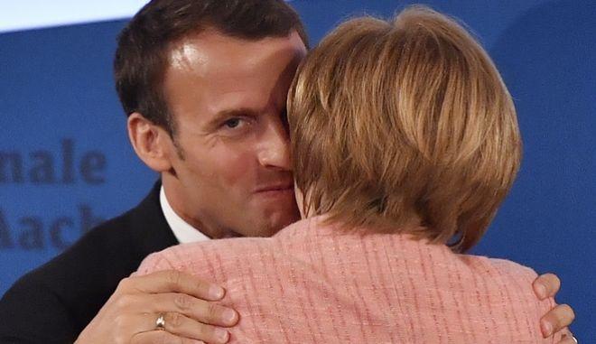 Ο Γάλλος πρόεδρος Εμμανουέλ Μακρόν και η Γερμανίδα καγκελάριος Ανγκελα Μέρκελ κατά την απονομή του βραβείου του Καρλομάγνου στον πρώτο, στο Άαχεν της Γερμανίας.