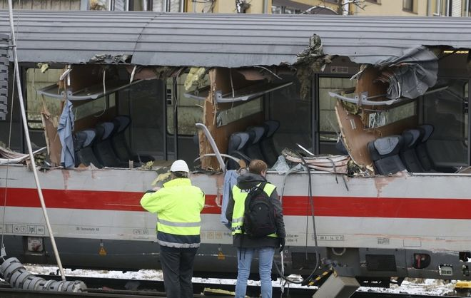 Rescuers  and rail workers stand at the scene of a train crash in Niklasdorf, Austria, Monday, Feb. 12, 2018. Two passenger trains collided near a station of Niklasdorf. Two passenger trains crashed in central Austria on Monday, killing one person and injuring more than 20 others, authorities said. One train hit the side of the other near the station in Niklasdorf, a town 60 kilometers (40 miles) north of Graz, said Graz police spokesman Leo Josefus. (AP Photo/Ronald Zak)