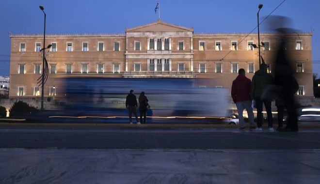 People stand in front of the Greek Parliament, as vehicles drive past, in central Athens, on Tuesday, Nov. 21, 2017. Lawmakers are preparing for a debate on the 2018 budget, expected to be the last under an international bailout, but the government has promised it will maintain high primary surpluses and painful austerity measures, in the hope of winning more favorable debt repayment terms. (AP Photo/Petros Giannakouris)
