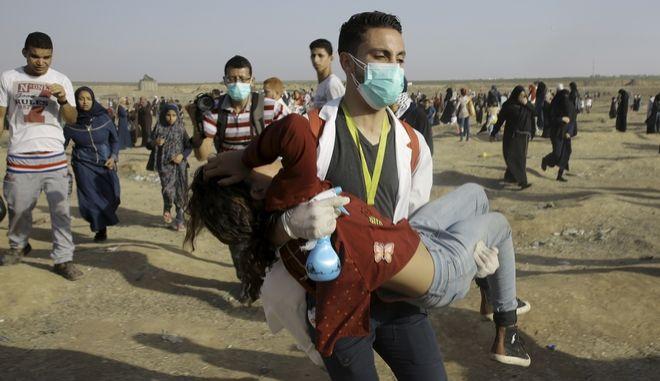 Παλαιστίνιος διασώστης απομακρύνει τραυματισμένη γυναίκα από διαδήλωση στη Λωρίδα της Γάζας
