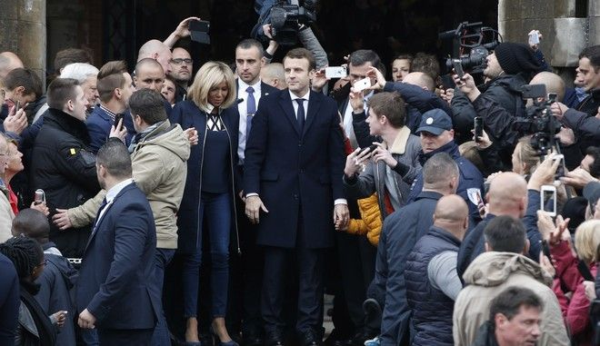 French independent centrist presidential candidate, Emmanuel Macron and his wife Brigitte are greeted by supporters after casting his vote in Le Touquet, France, Sunday, May 7, 2017. Voters across France are choosing a new president in an unusually tense and important election that could decide Europe's future, making a stark choice between pro-business progressive Emmanuel Macron and far-right populist Marine Le Pen. (AP Photo/Thibault Camus)