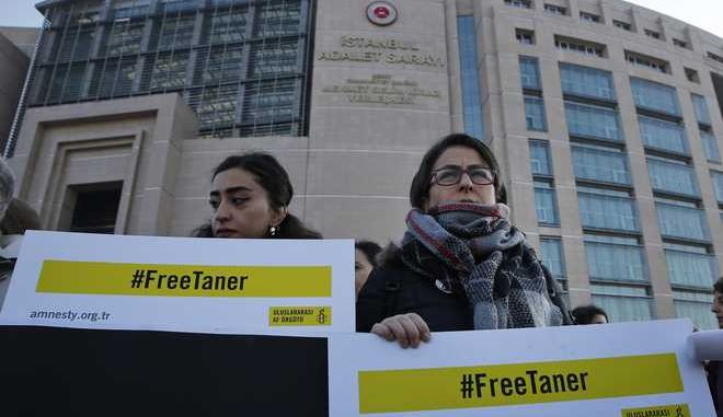 Human rights activists stage a protest outside a court in Istanbul, Wednesday, Jan. 31, 2018, where the trial of eleven human rights activists accused of belonging to and aiding terror groups is ongoing. The protesters demand the release of Amnesty's Turkey chairman Taner Kilic, who was imprisoned separately in June 2017, and goes on trial in the city of Izmir for alleged links to U.S.-based cleric Fethullah Gulen, blamed by the government for last year's coup attempt. (AP Photo/Lefteris Pitarakis)