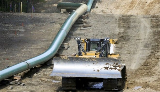 An operator moves a bulldozer along a section of assembled pipe lined up along a cleared section of woods where a pipeline for shale gas is under construction on Saturday, July 8, 2017, in Jackson Township, Pa.(AP Photo/Keith Srakocic)